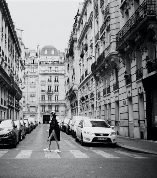 Monochrome Photo of Woman Walking On Pedestrian Lane