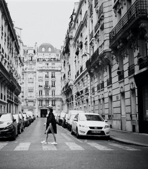 Монохромное фото женщины, идущей по пешеходной дорожке