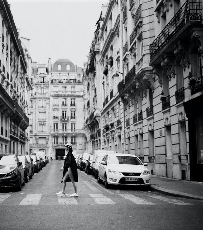 Monochrome Photo of Woman Walking On Pedestrian Lane