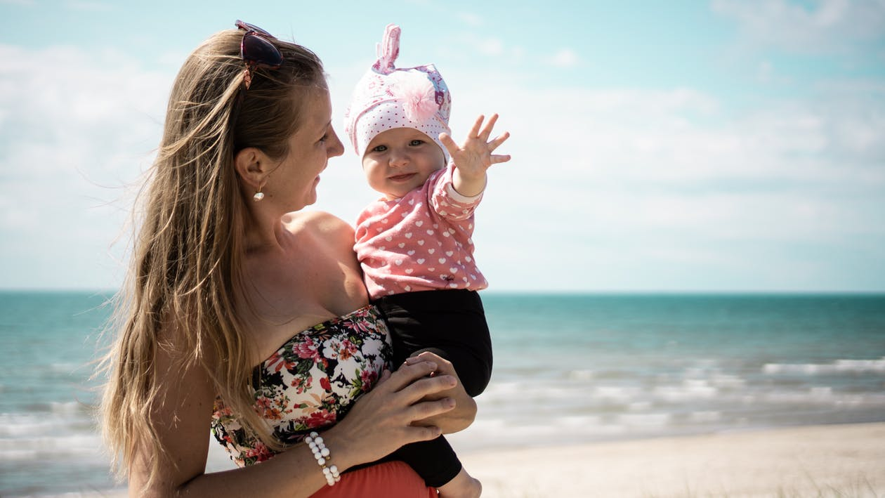 Woman Carrying Baby On Shore