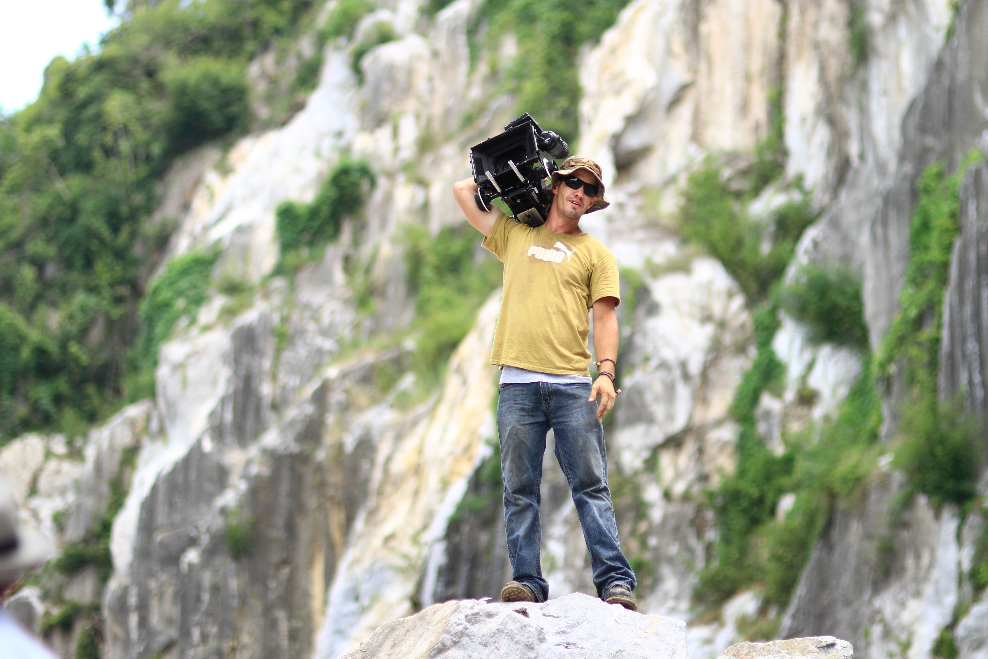 Man Standing on Rock While Holding Black Case