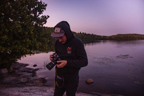 Man Holding Camera While Standing Near Body Of Water