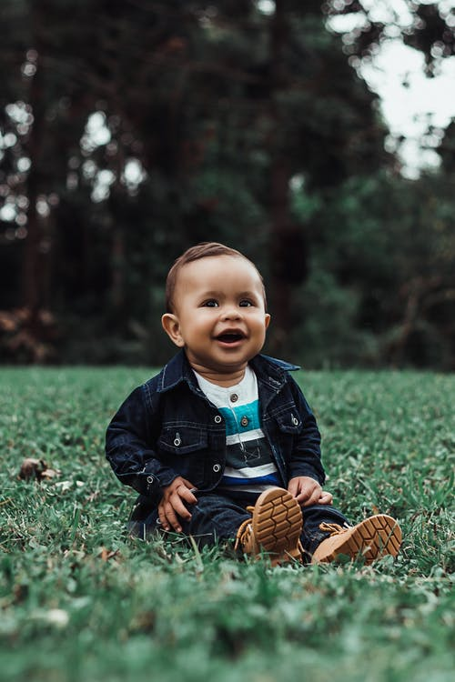 Photo of Smiling Baby Boy in Denim Outfit Sitting on Grass