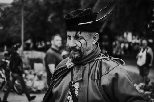Photo Monochrome D'un Homme Portant Un Chapeau Avec Plume