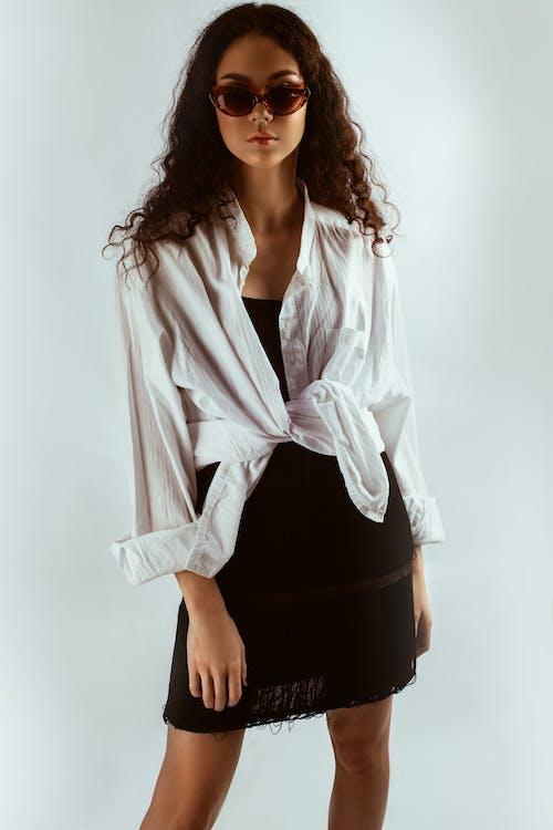 Photo De Femme En Chemise Blanche, Robe Noire Et Lunettes De Soleil Posant Devant Fond Blanc