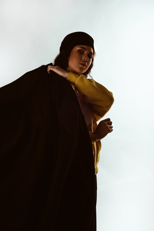 Photo of Woman in Yellow Hoodie, Black Beret Hat, and Black Coat Posing In Front of White Background