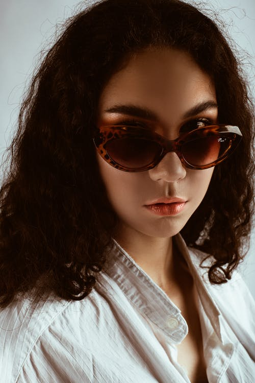 Portrait Photo of Woman in Sunglasses and White Shirt Posing