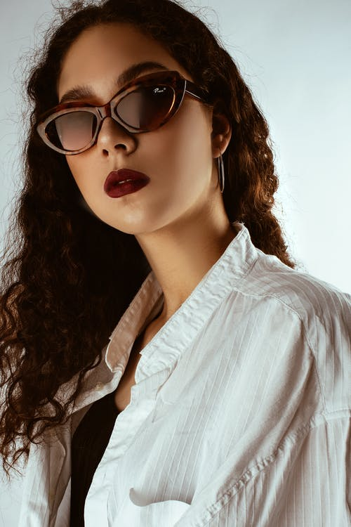 Portrait Photo of Woman in Sunglasses and Red Lipstick Posing In Front of White Background