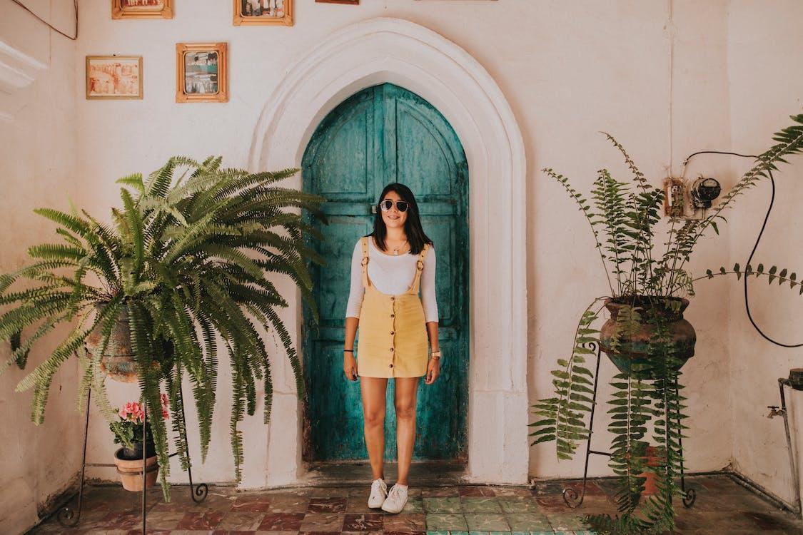 Woman Wearing Yellow Dungaree Skirt Standing in Front of Green Wooden Door