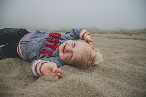 Photo of Boy Lying on Sand