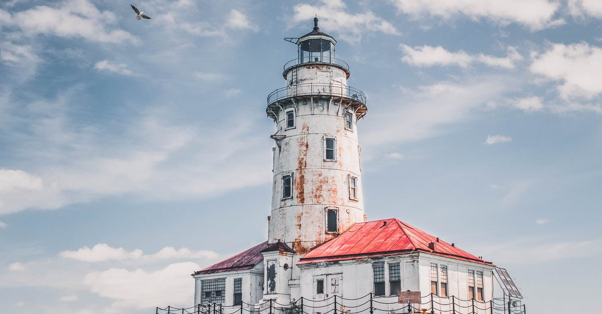 White Lighthouse Under Cloudy Sky · Free Stock Photo