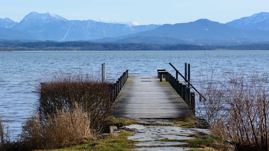 wooden jetty on a lake with mountain