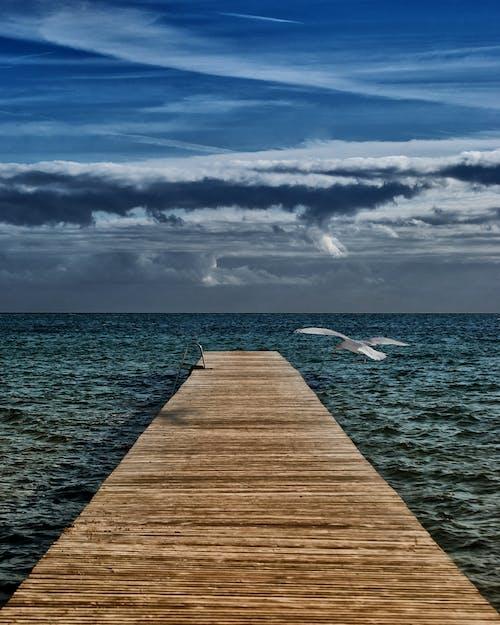 ahşap geçit, ahşap iskele, bulutlar, deniz içeren Ücretsiz stok fotoğraf