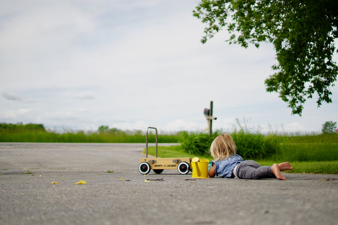 Girl Lying on Road in Front of Cart