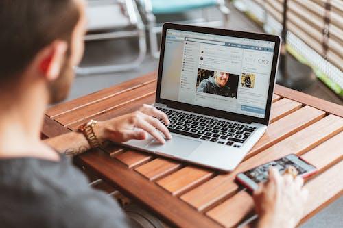 Uomo Seduto Davanti Al Macbook Pro Acceso