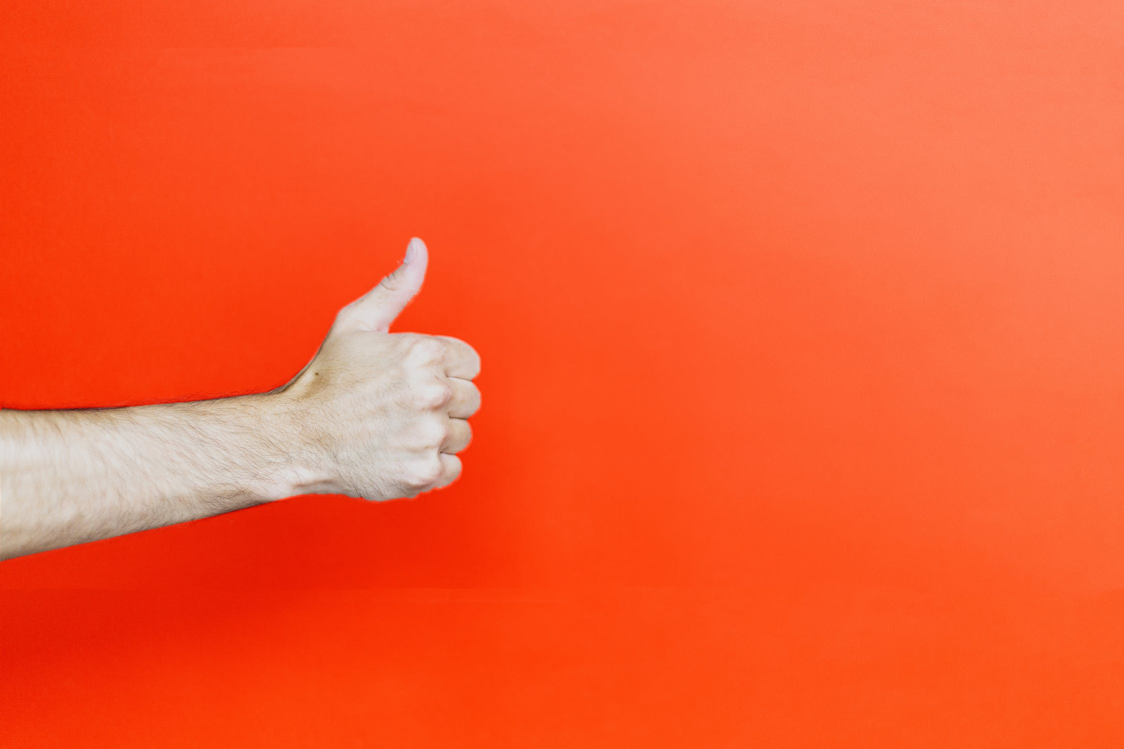 A person giving a thumbs up in front of a red background. Photo by pexels user Oleg Magni. Photo used courtesy of pexels.com