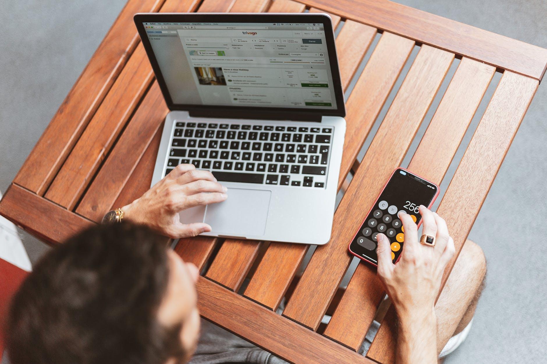 personne qui utilise la calculatrice de son téléphone tout en surfant sur internet