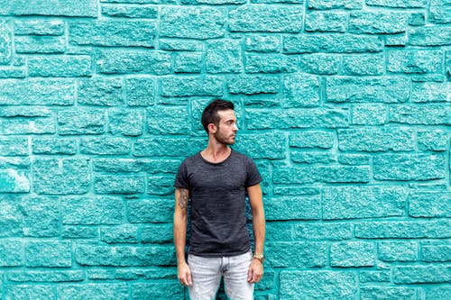 Man Standing Beside Teal Wall