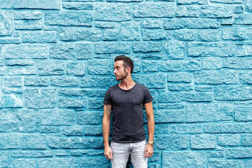 Photo of Guy Standing In Front Of Blue Wall