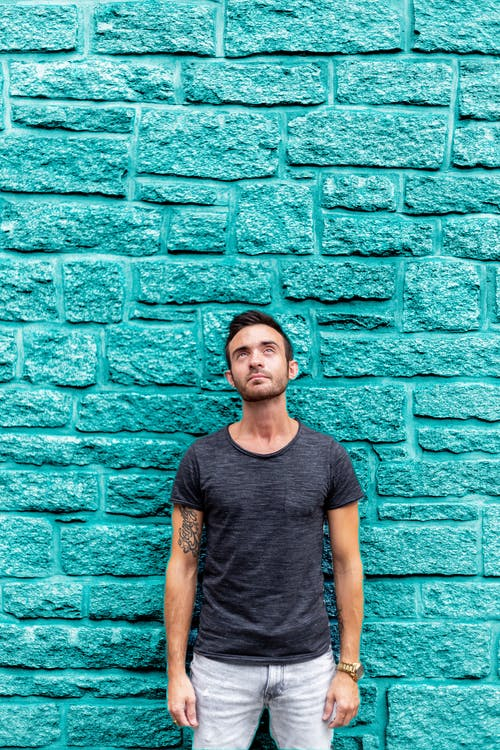 Man Standing in Front of Teal Concrete Wall