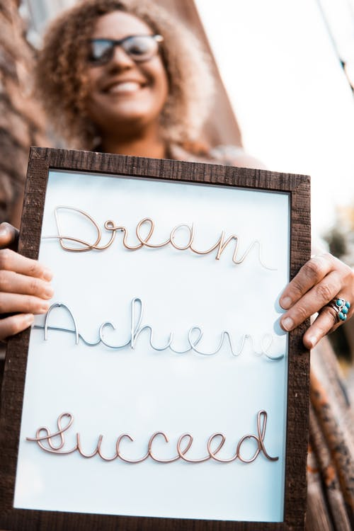 Woman Holding Brown Wooden Frame With Dream Achieve Succeed