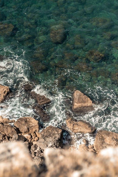 Foamy sea waving near rocky cliff