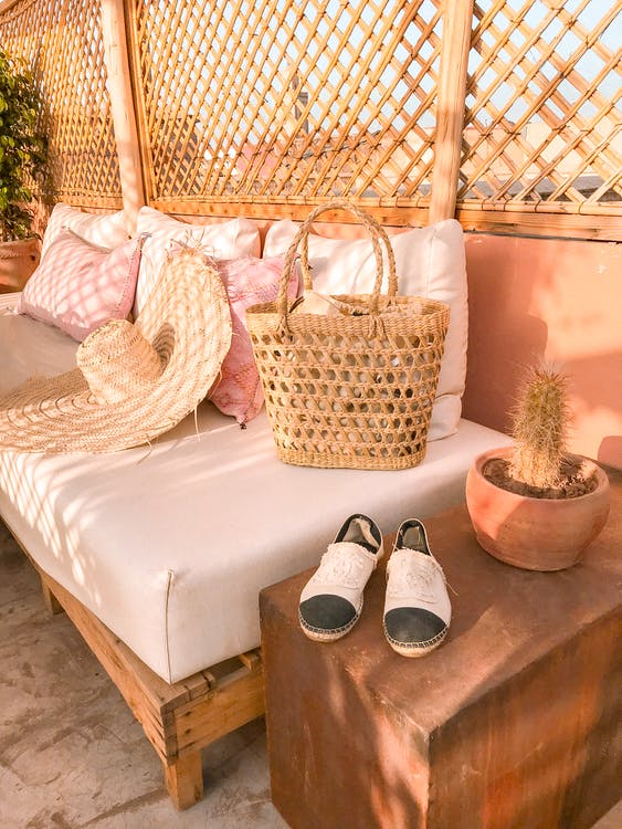 Photo Of Wicker Bag and Straw Hat On Top Of The Sofa