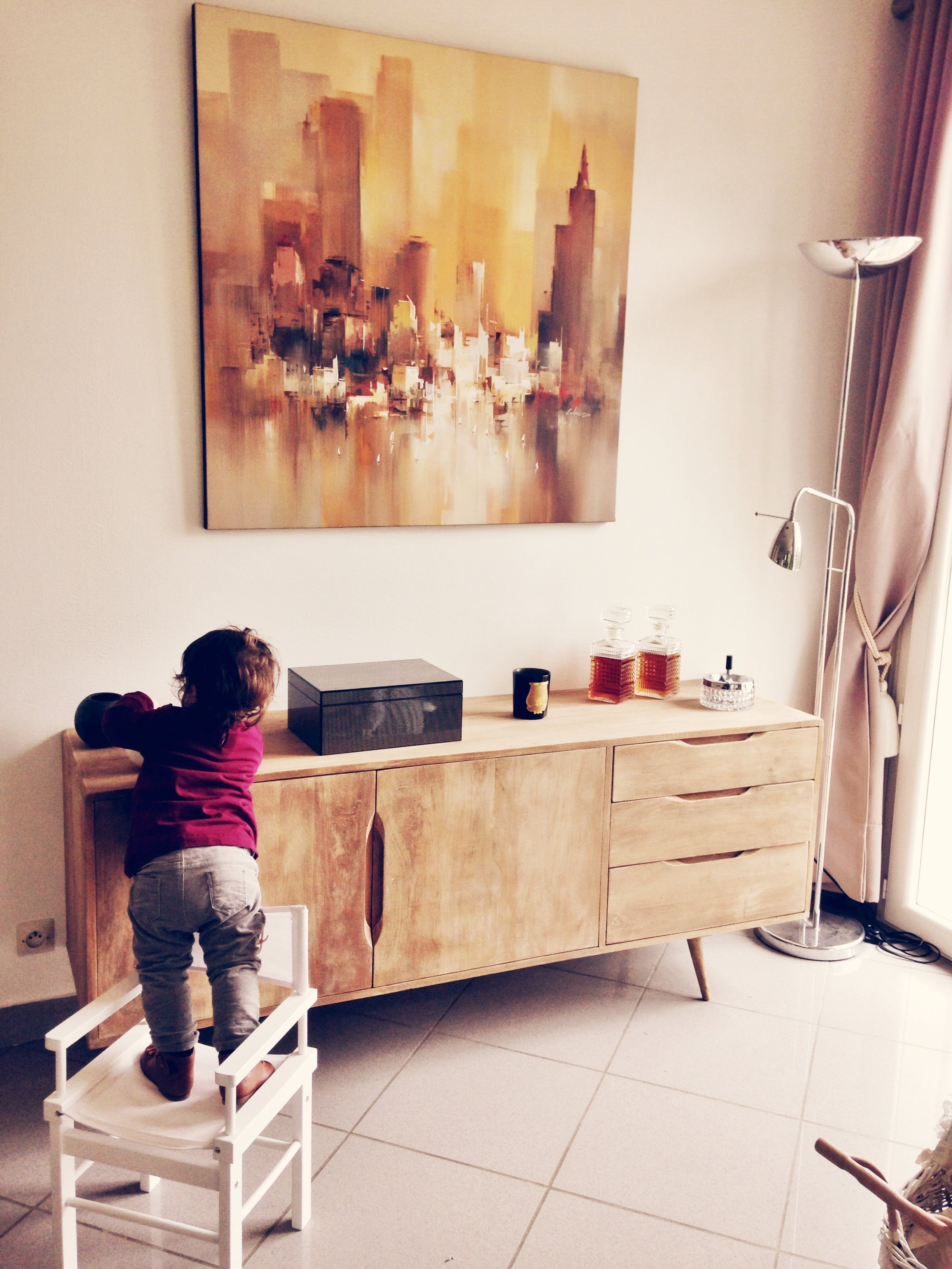 Toddler Standing on White Chair Beside Sideboard