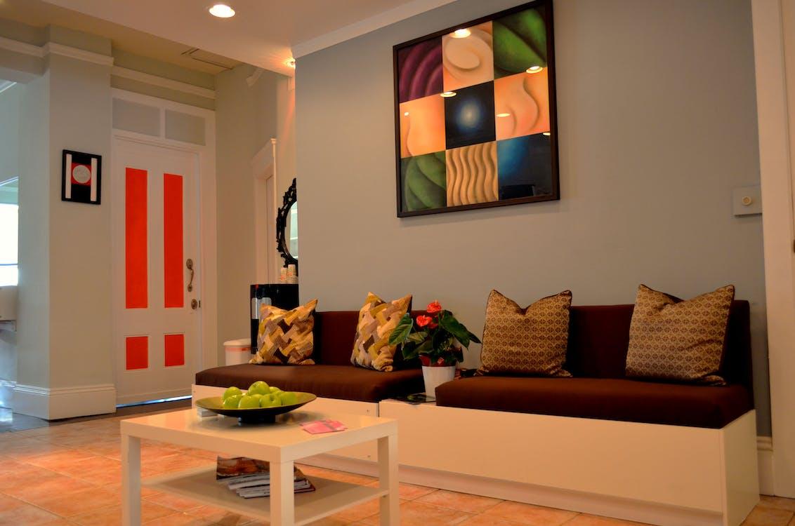 Maroon Sofa Under Abstract Painting on Gray Wall
