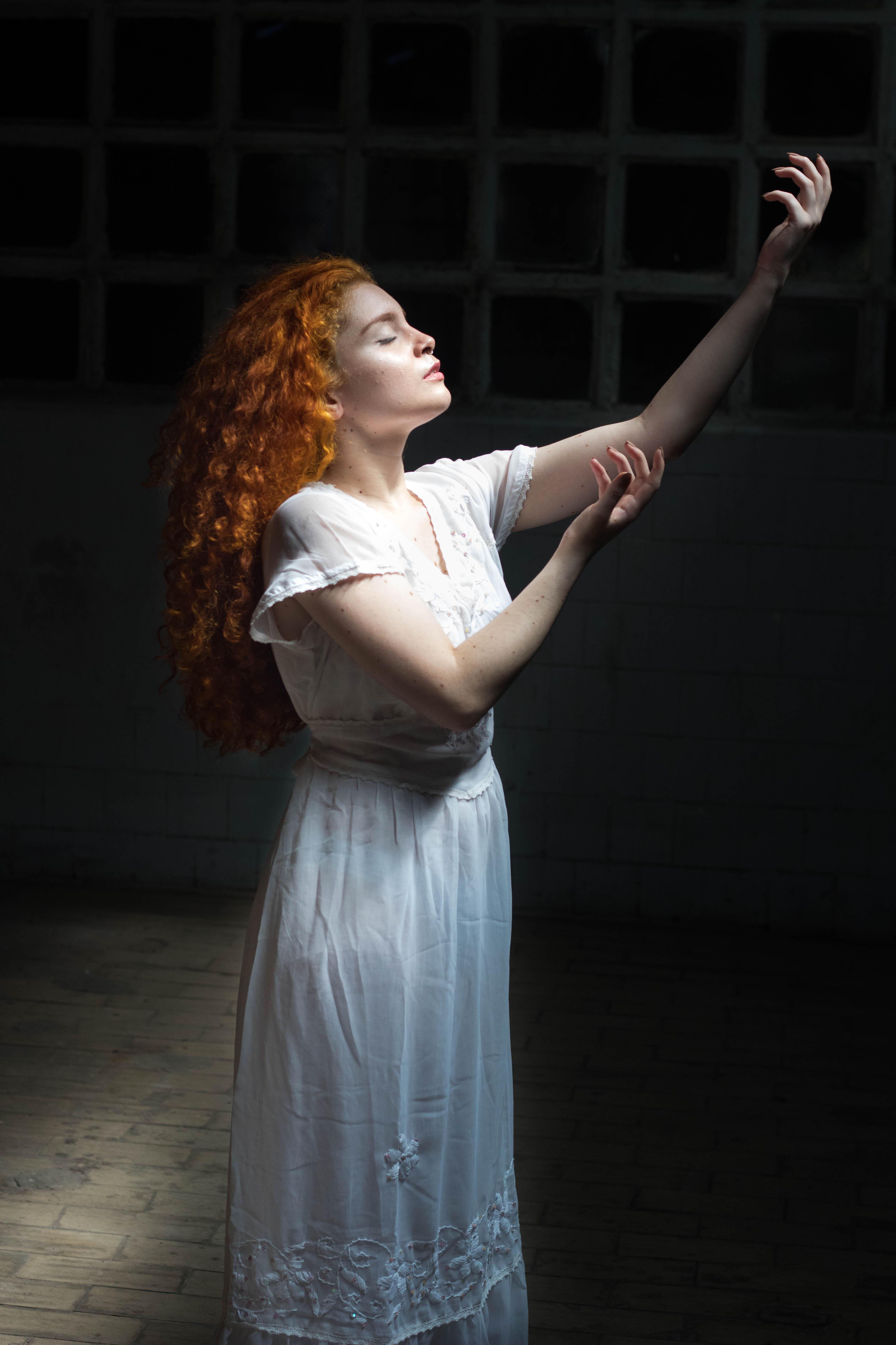 Woman Wearing White Dress Raising Her Hands