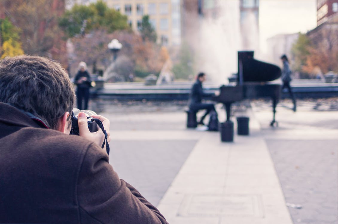 Man Taking a Photo of Person Playing Piano