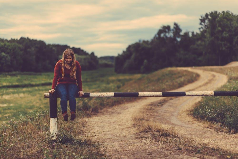 Woman sitting on a metal gate pass | Photo: Pexels