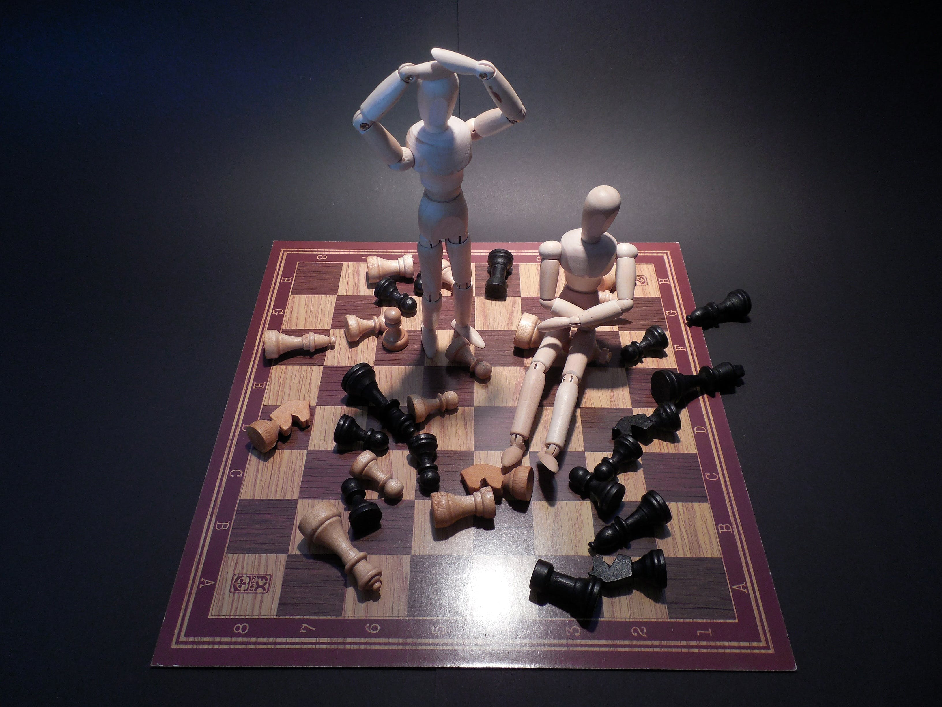 wooden figurines on chessboard with scattered chess pieces