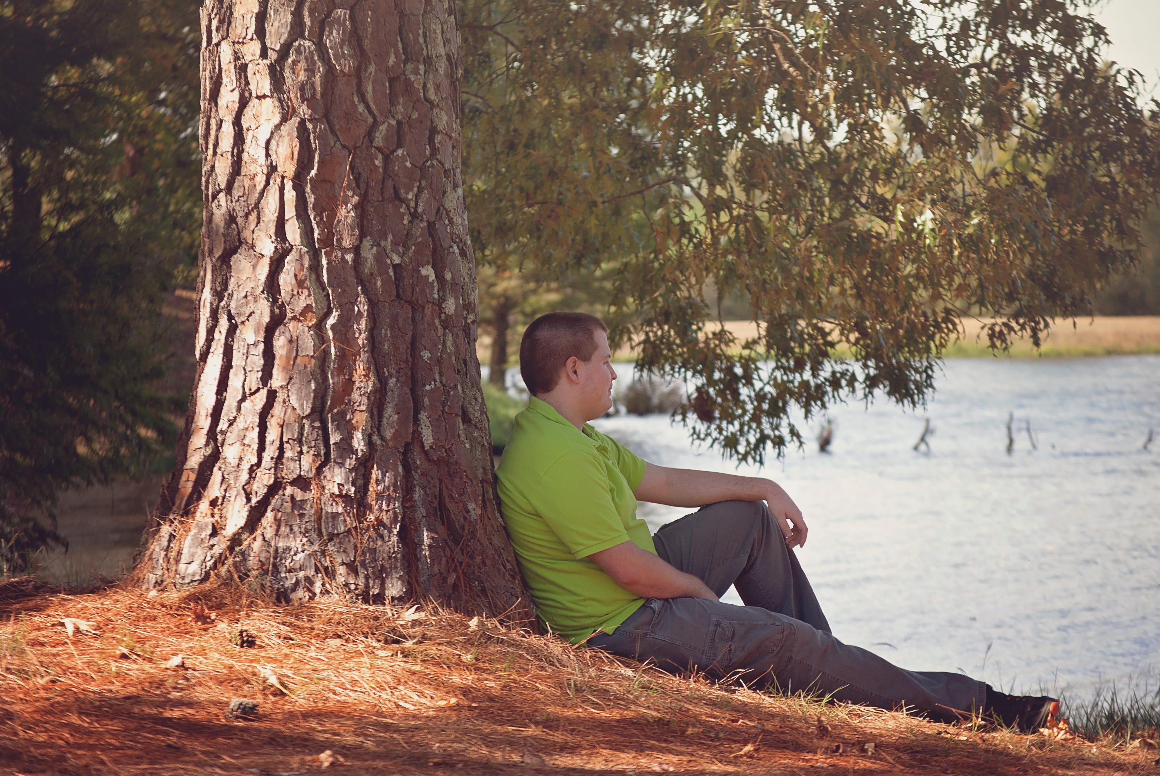 Man in Green Polo Shirt Sitting Beside Tree