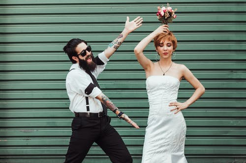 Photo of Couple Posing Near Roller Shutter