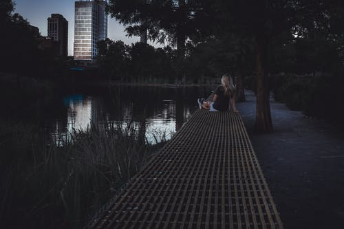 Photo of Woman Sitting Near Lake