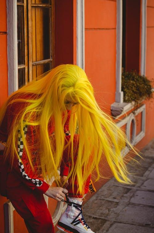 Woman Leaning on Orange Wall