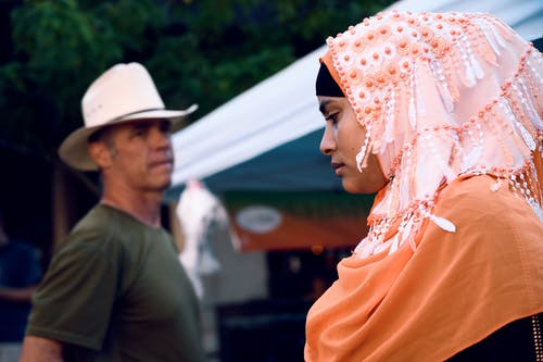 Man Wearing Cowboy Hat Looking At A Woman