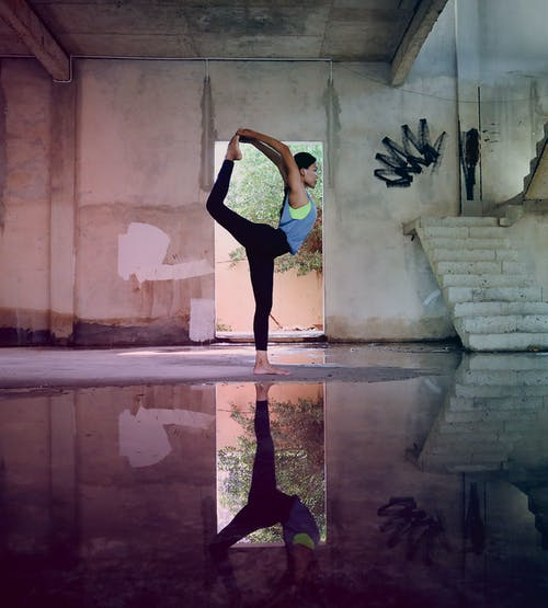 Reflection of Woman Doing Yoga Pose Near Puddle