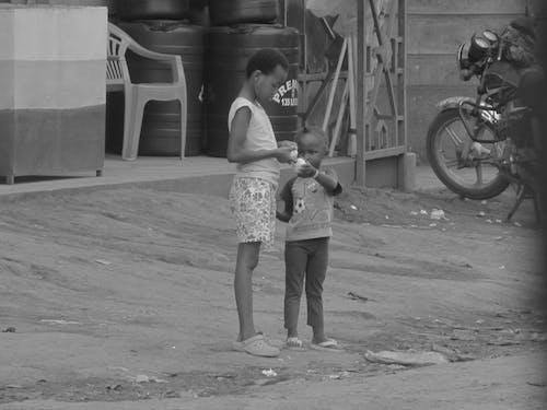 Free stock photo of two children sharing an orange