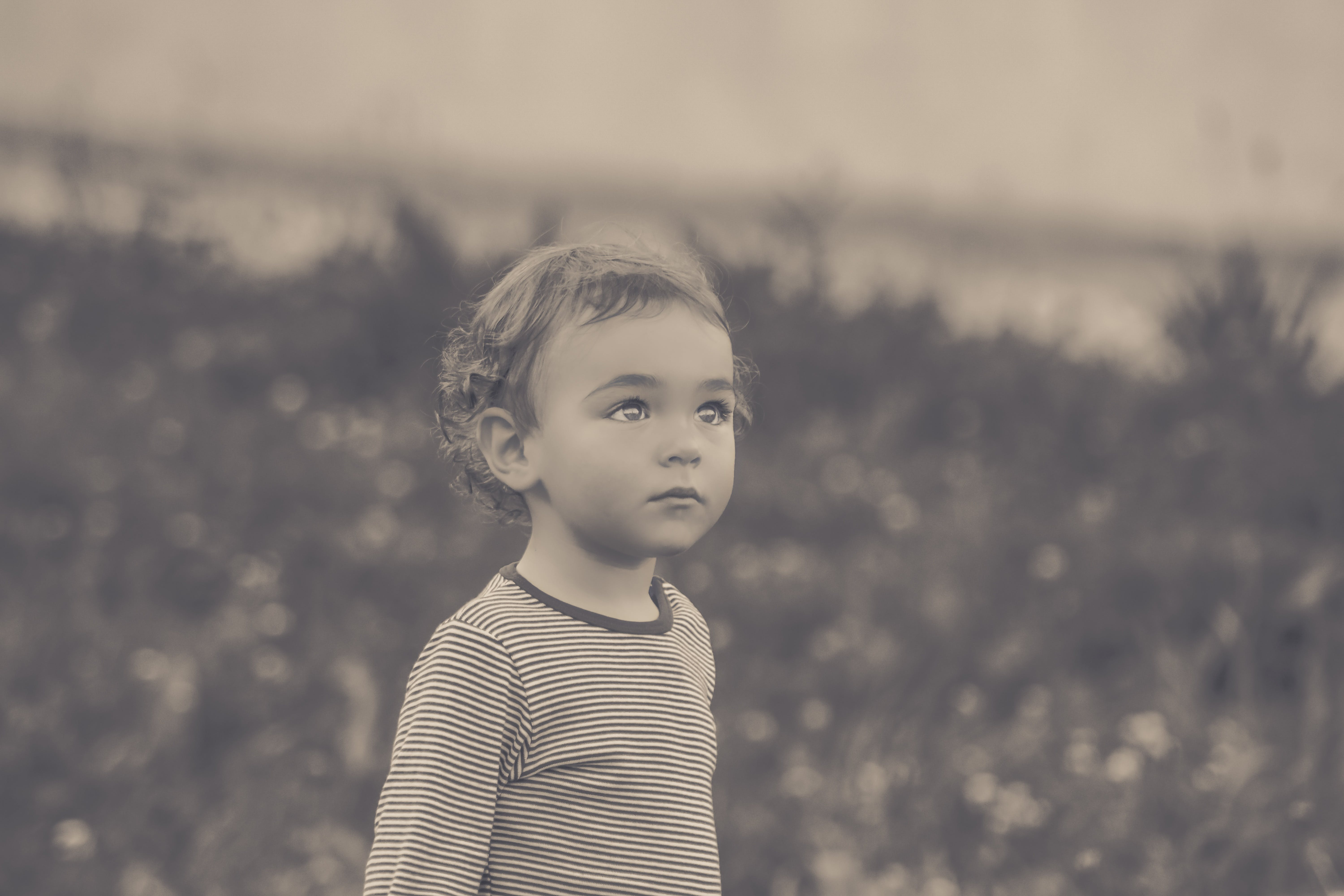 Selective Focus Grayscale Photo of Boy Looking Up