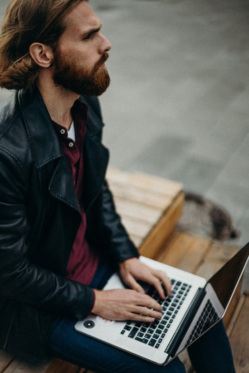 Man Wearing Leather Jacket Using Laptop