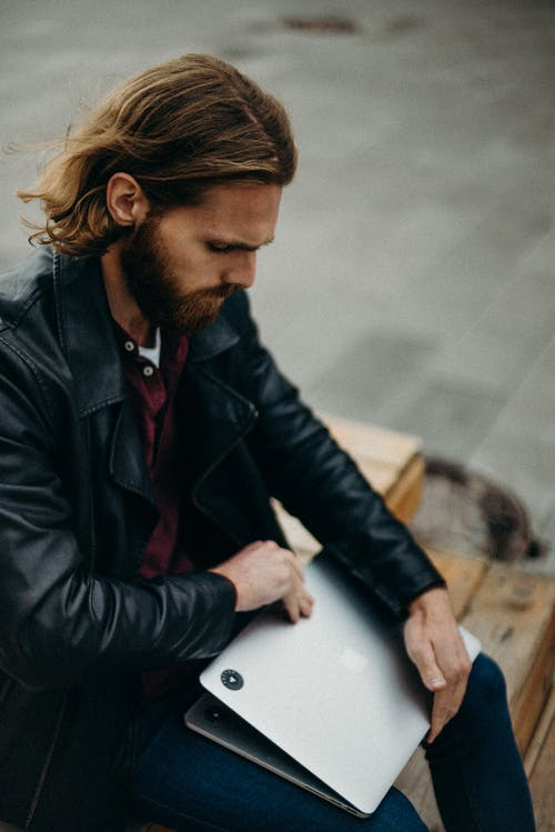 Man in Black Leather Jacket Holding Silver Macbook