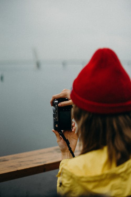 Woman Wearing Red Knit Cap While Holding Camera
