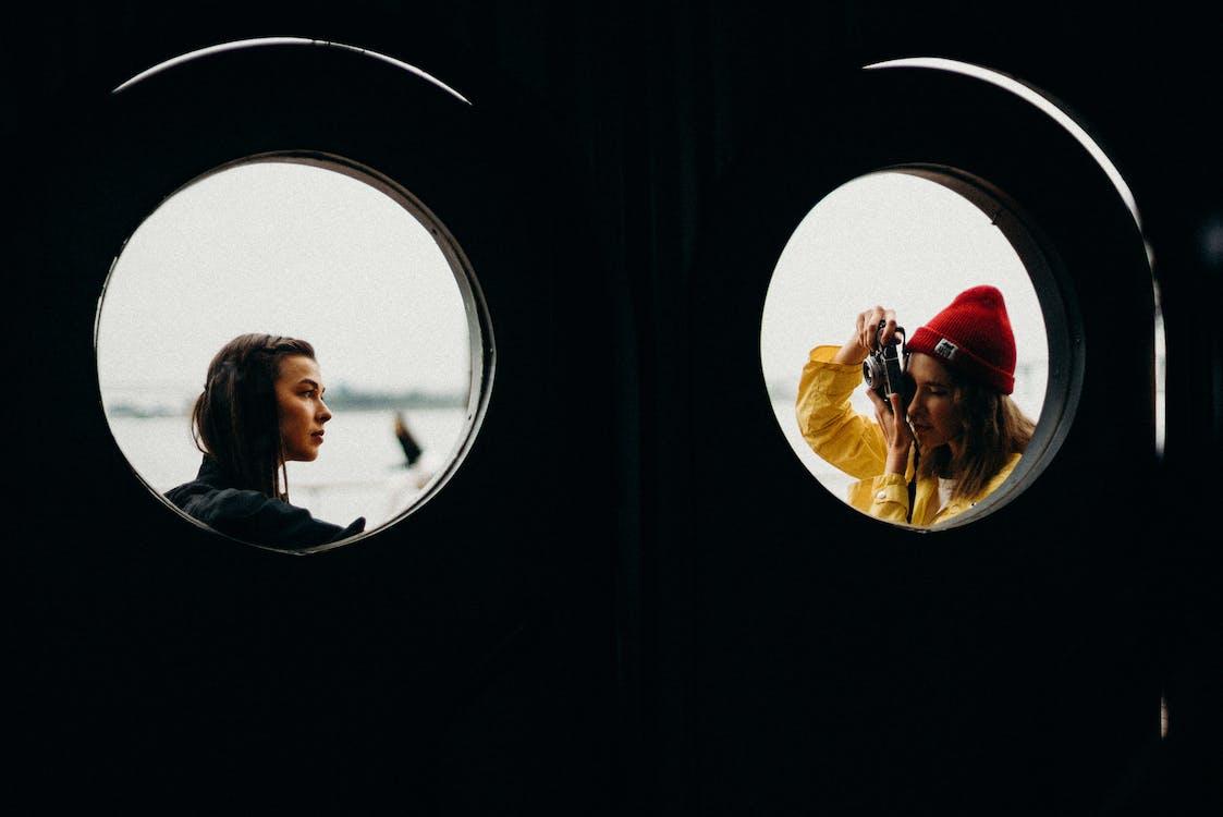 Two Women Near Windowpane