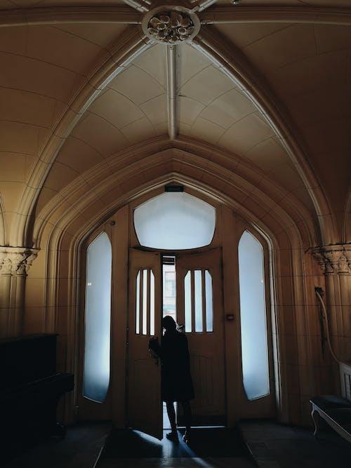 Woman Standing by an Open Door