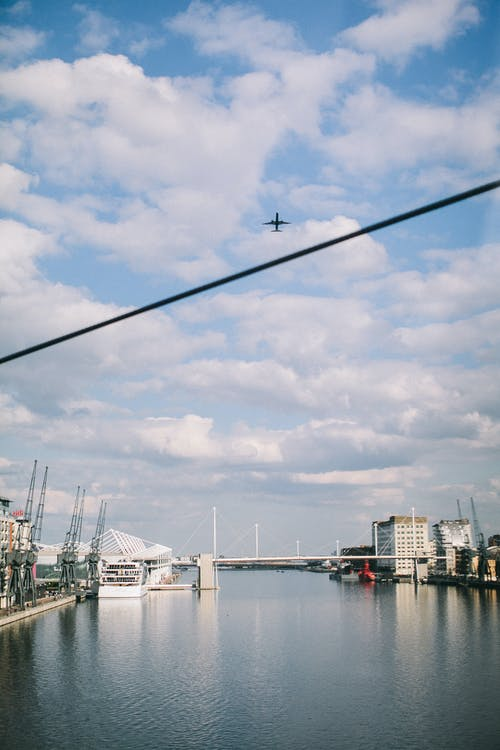 Airplane Flying Over Harbor