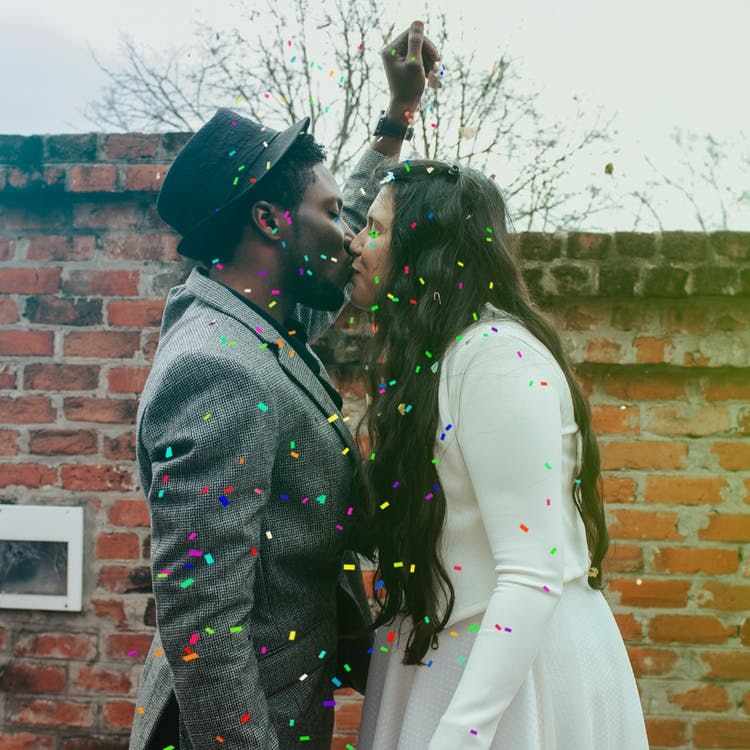 Man in Hat Kissing Woman in White Dress