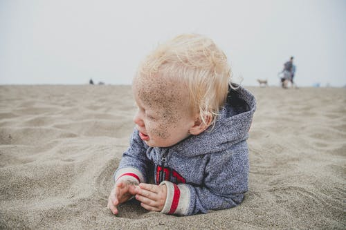 Child Lying on Sand With Sand over His Face
