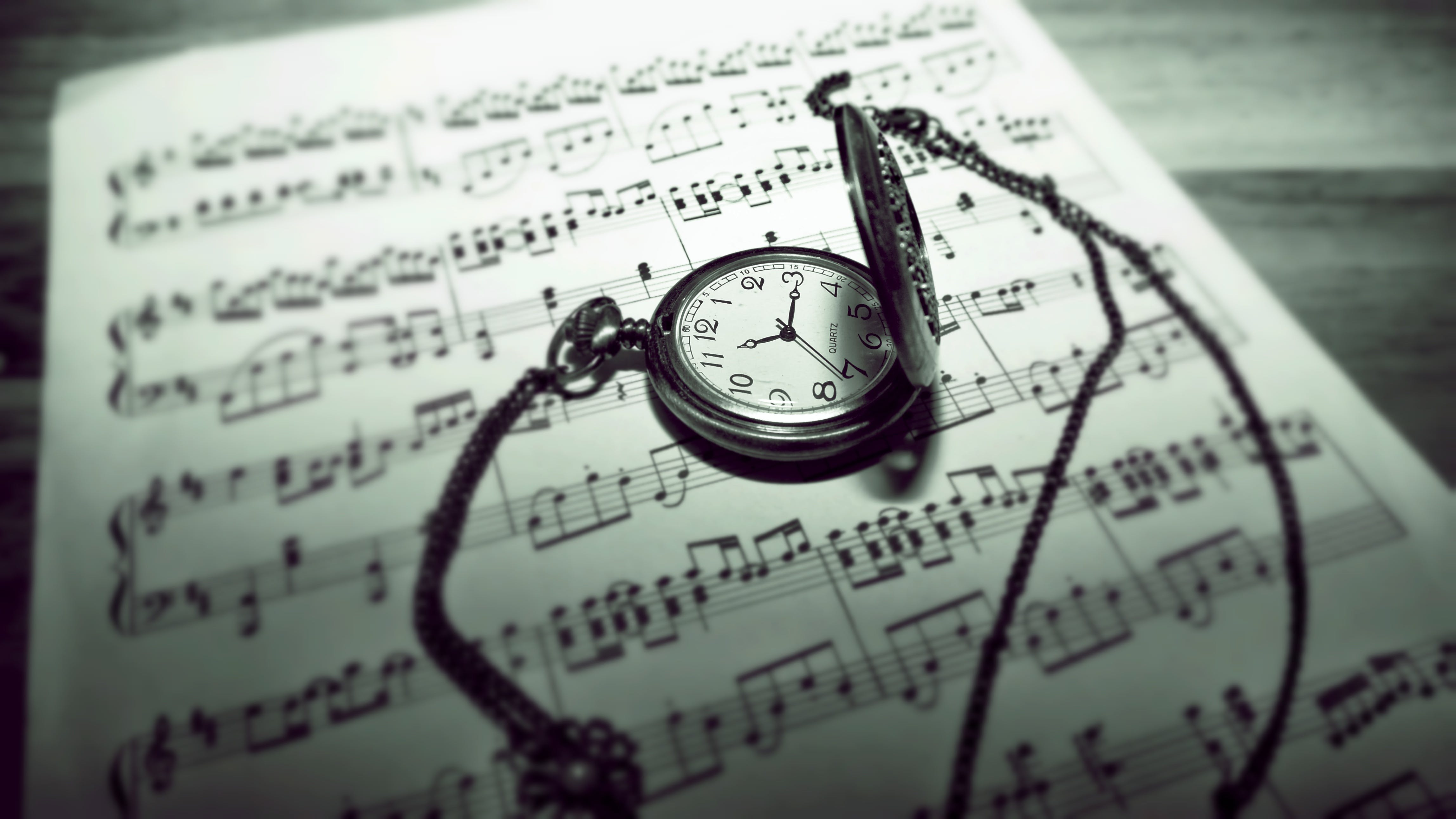 Round Gray Pocket Watch Reading 11:15 Placed on Music Sheet